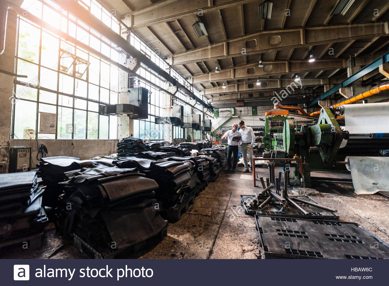 Colleagues inspecting rubber in tyre manufacturing plant, Ballenstedt, Germany - Stock Image