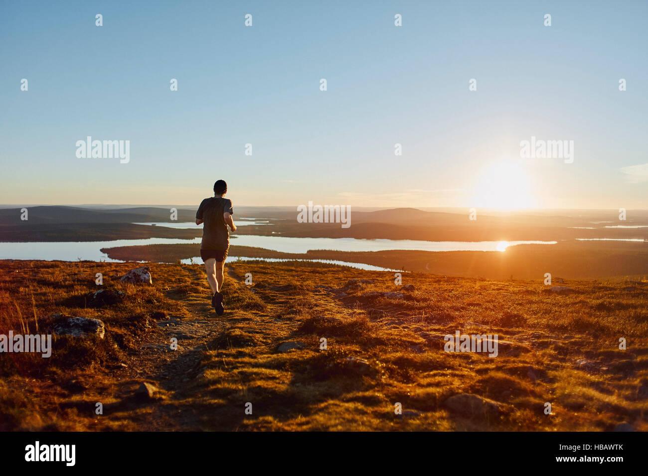 Man running on cliff top at sunset, Keimiotunturi, Lapland, Finland - Stock Image