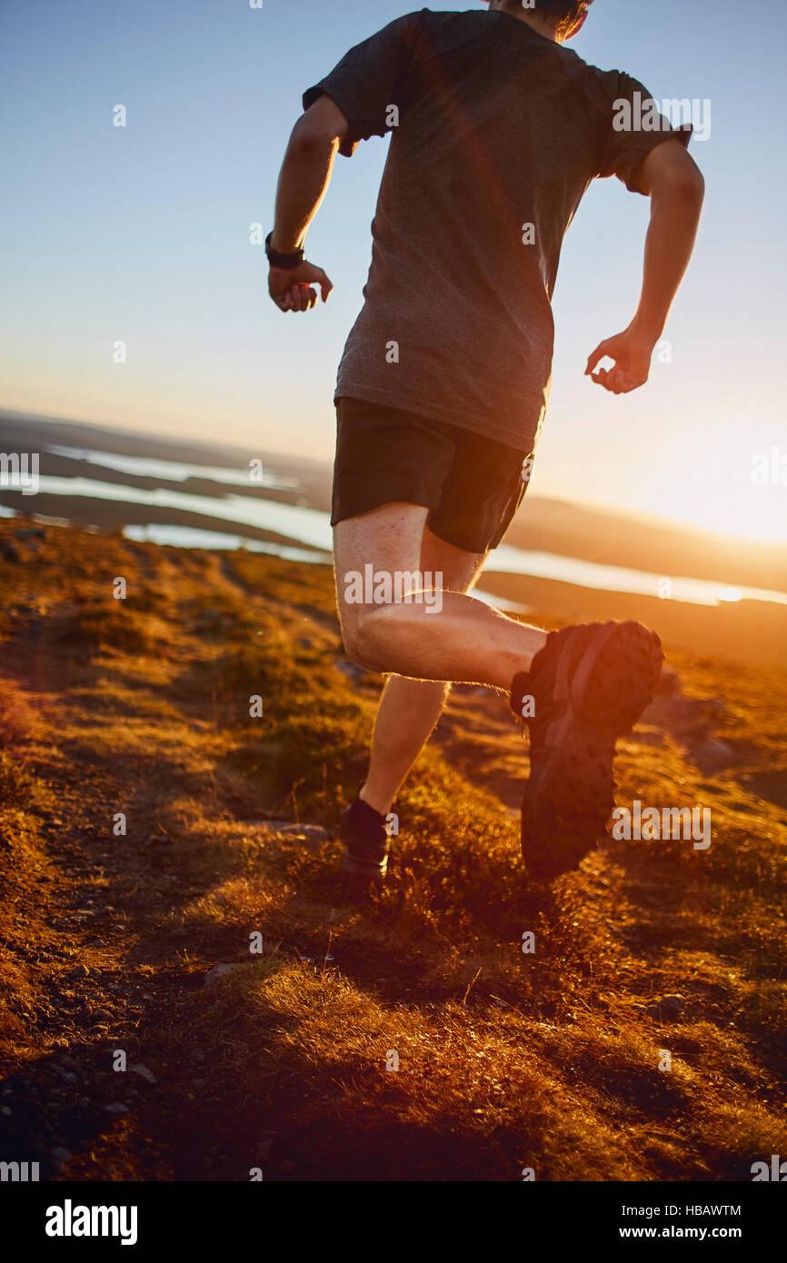Man running on cliff top at sunset, Keimiotunturi, Lapland, Finland Stock Photo
