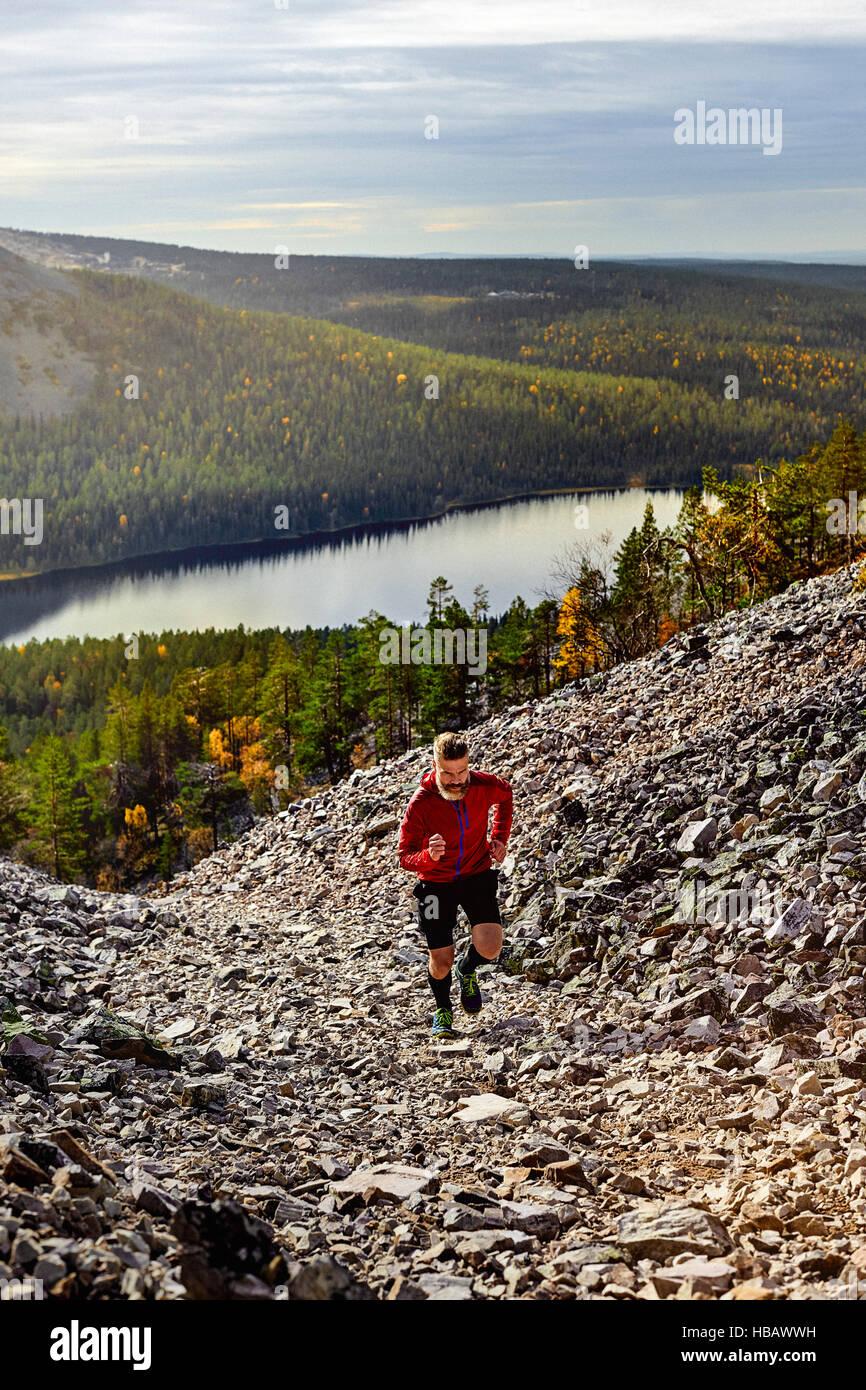 Hiker running up steep hill, Kesankitunturi, Lapland, Finland - Stock Image