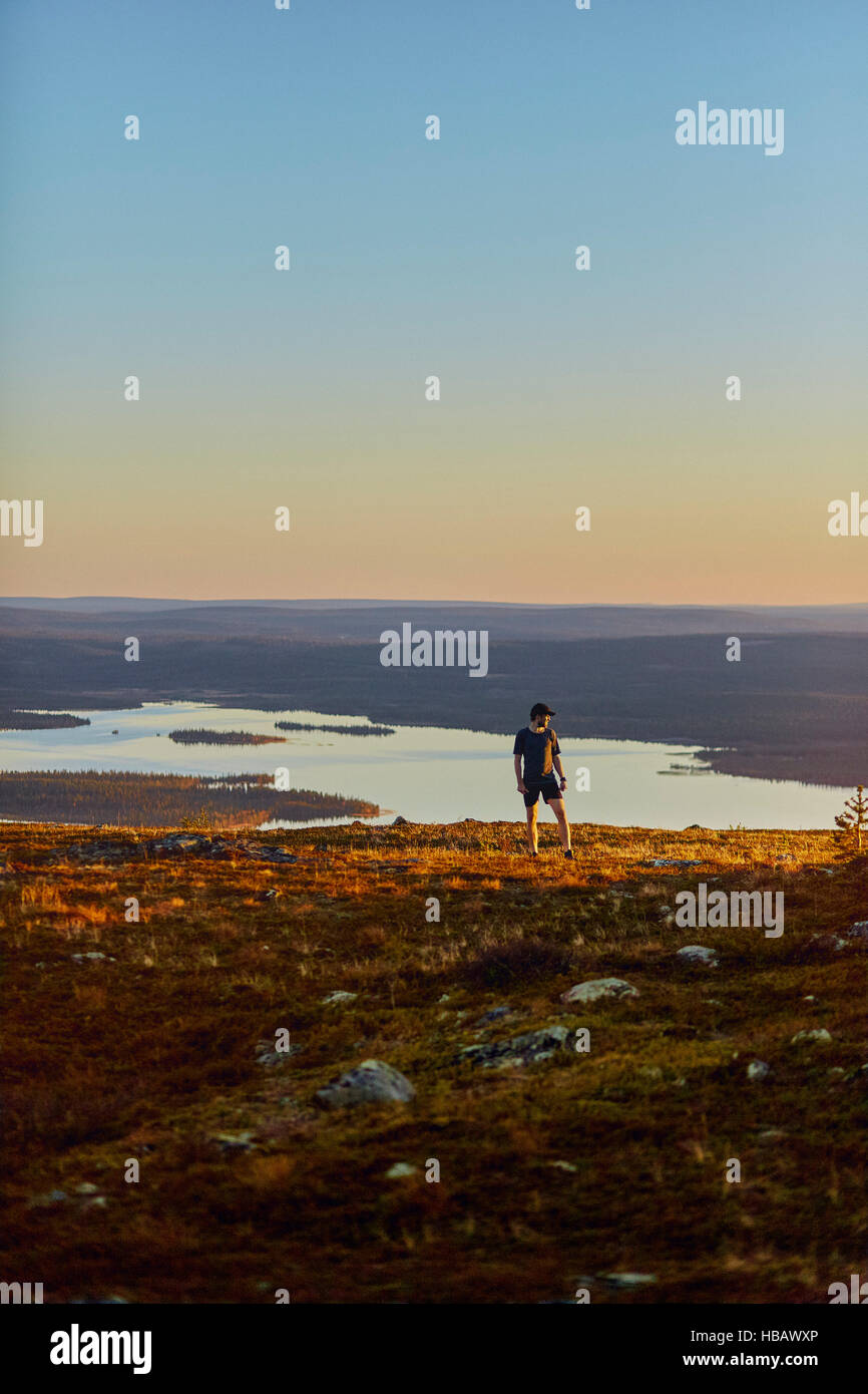 Man resting after running on cliff top at sunset, Keimiotunturi, Lapland, Finland - Stock Image