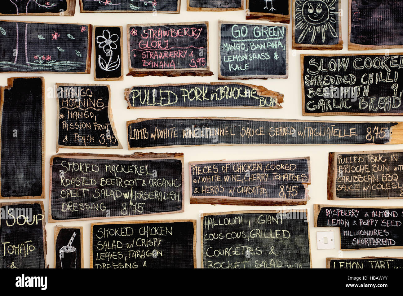 Quirky coffee shop interior with menu on chalked blackboards - Stock Image