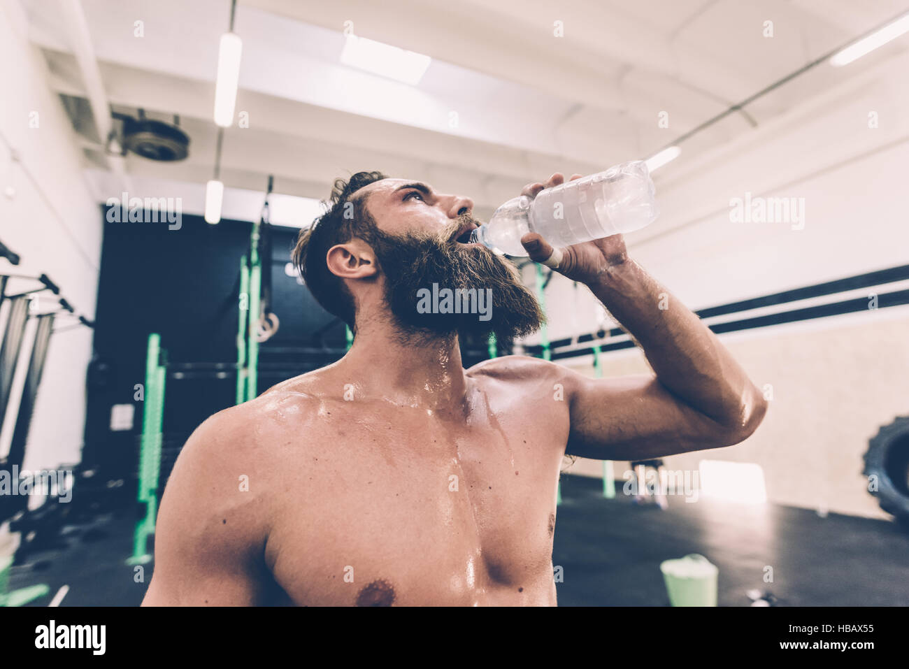 Exhausted male cross trainer drinking water in gym Stock Photo