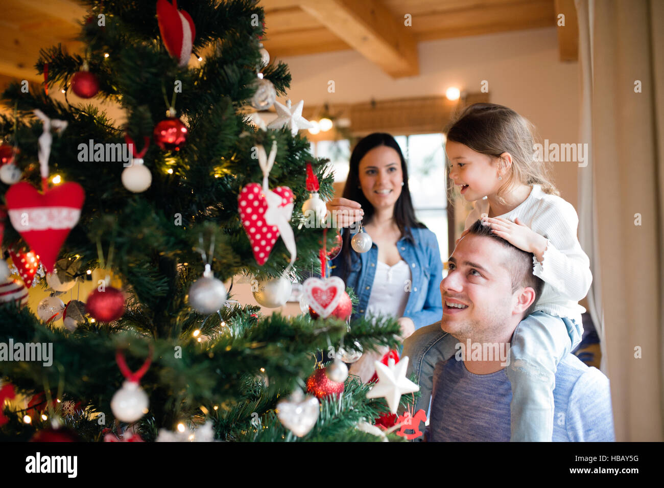 Young family with daugter at Christmas tree at home. - Stock Image