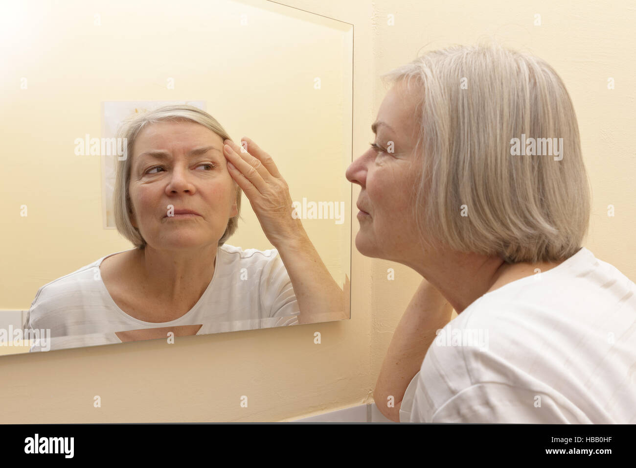 Elderly woman with gray hair examining her facial skin in the mirror of her yellow bathroom - Stock Image