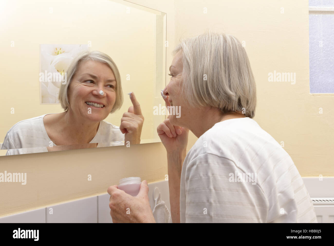 Old woman with a big smile and a cream spot on her nose in front of a mirror applying some moisturizer on her face - Stock Image