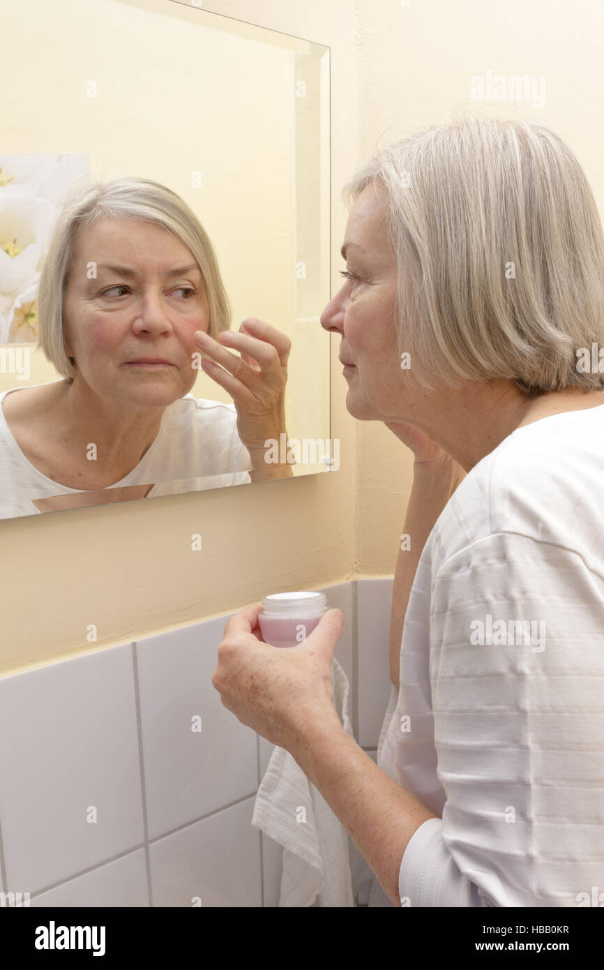 Elderly lady with a cream jar in hand standing in front of a mirror in a yellow bathroom and applying moisturizer - Stock Image