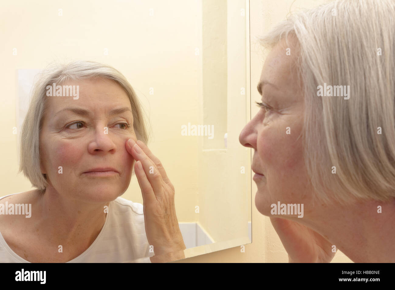 Senior woman with grey hair having a close look at the wrinkles of her facial skin in a mirror, thinking about esthetic - Stock Image