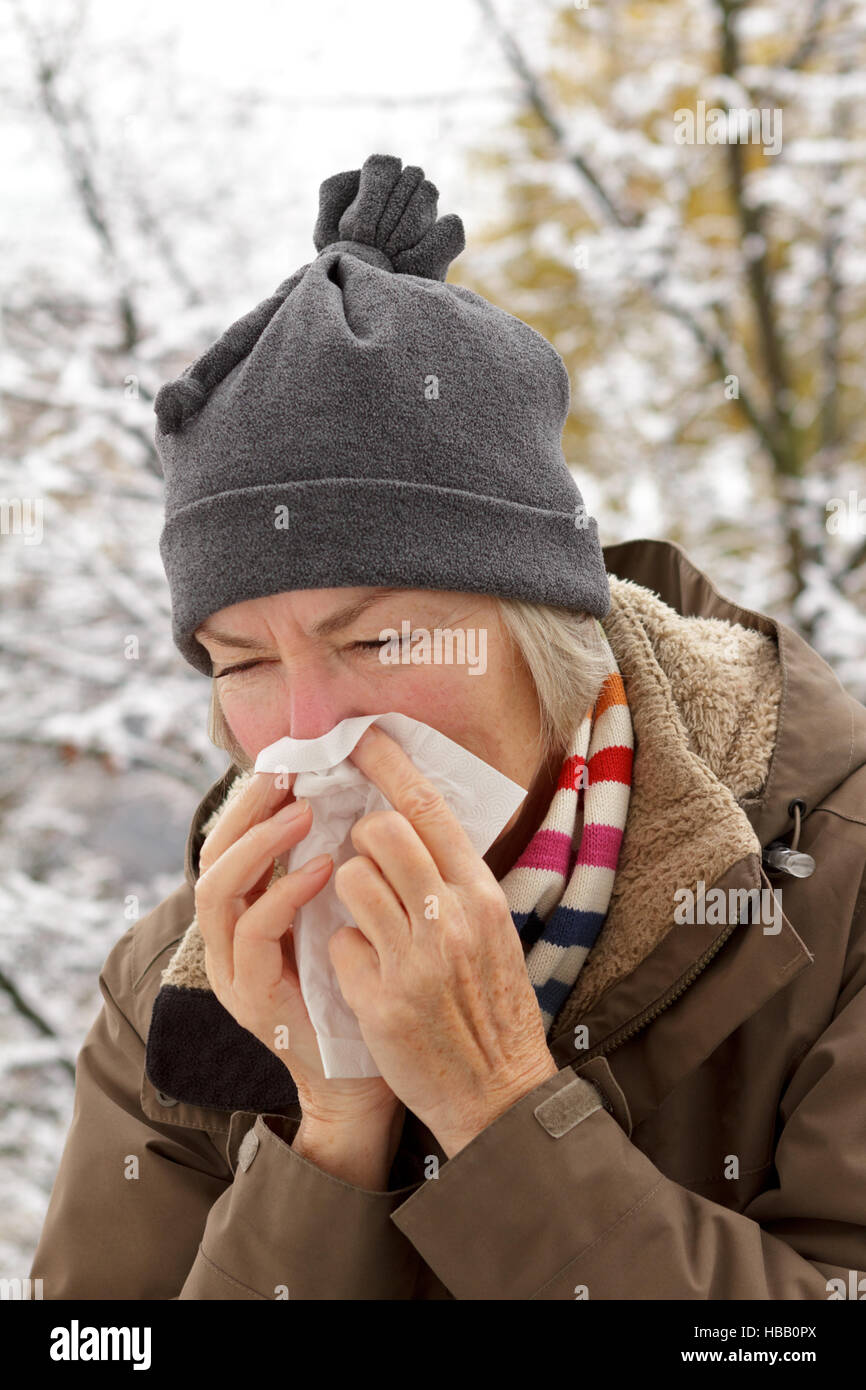 Senior woman with scarf and hat in a winter jacket blowing her nose into a paper tissue in front of a tree with - Stock Image