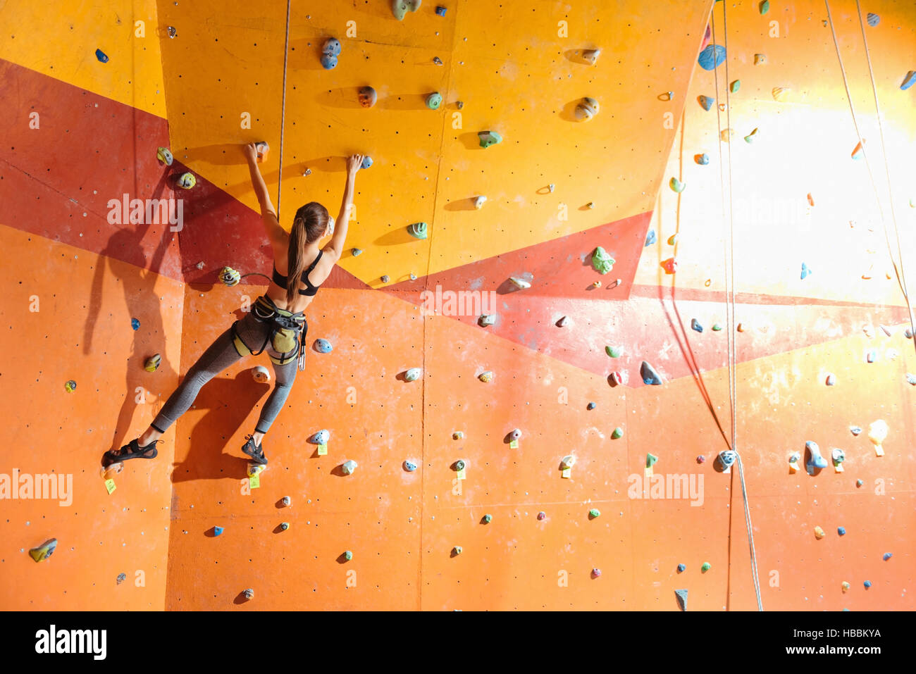 Slim woman climbing up special wall in gym - Stock Image