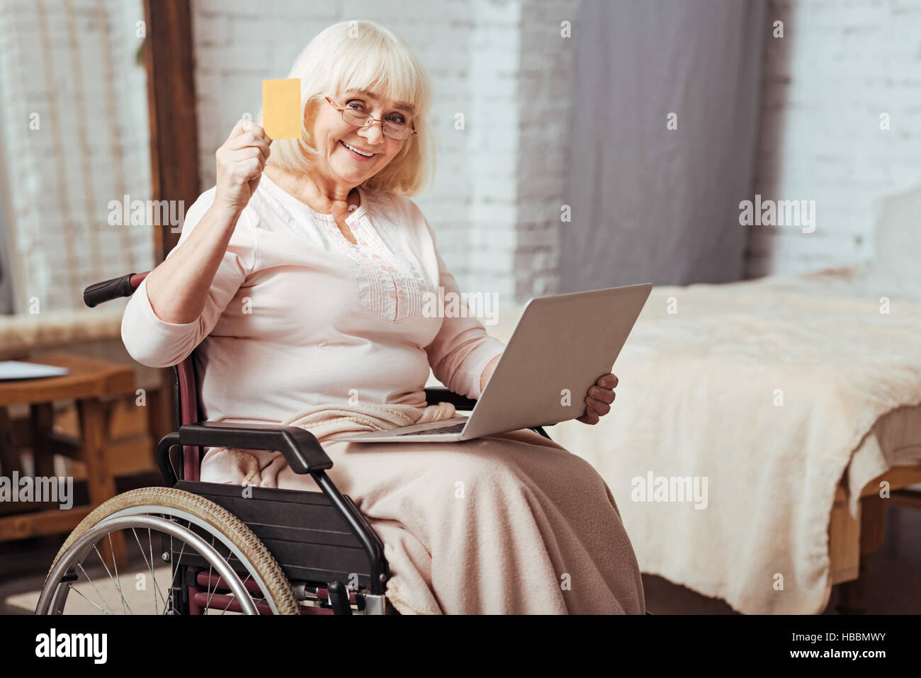 Positive elderly woman using laptop - Stock Image