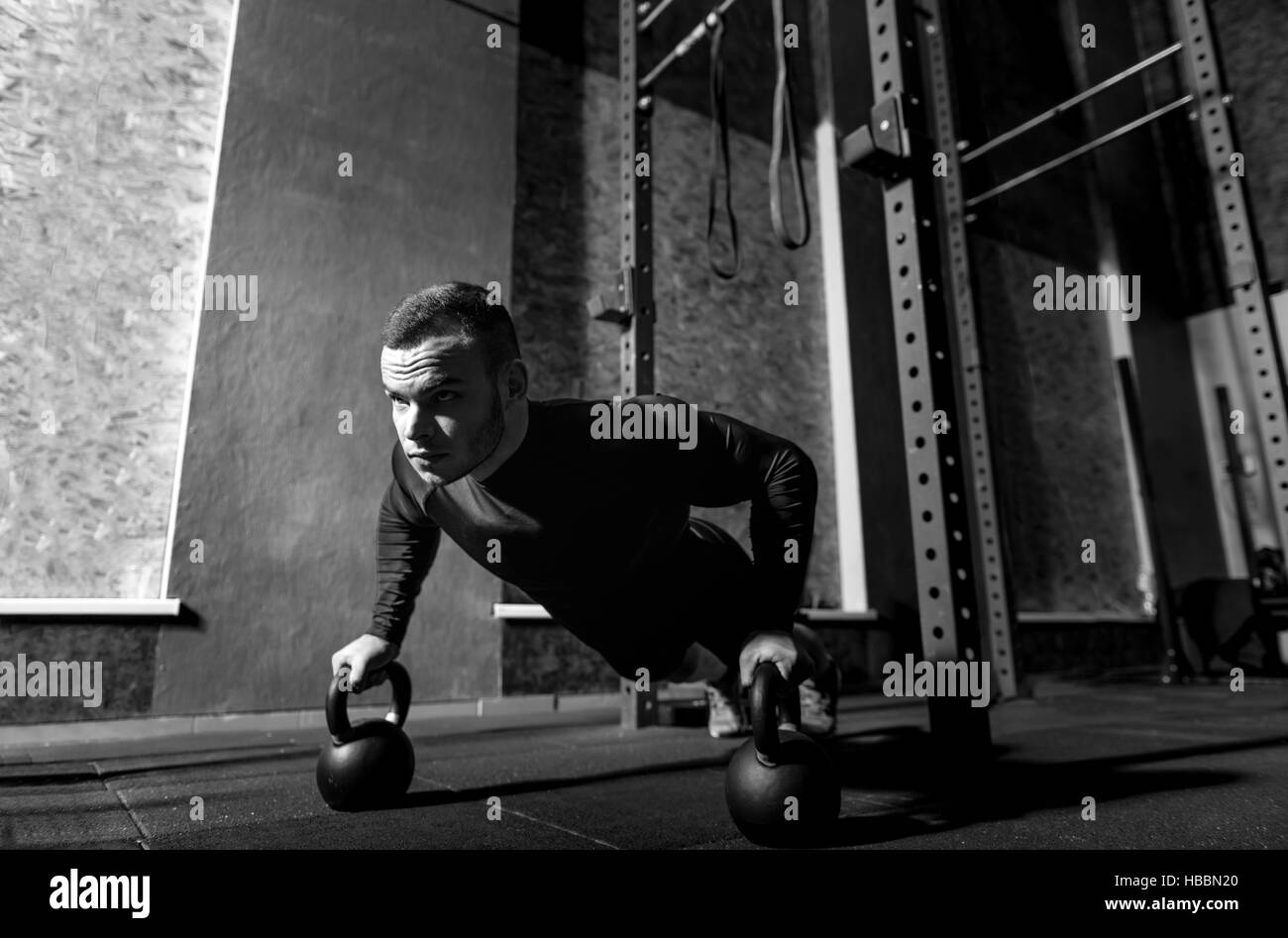 Well built brutal sportsman working out with kettlebells - Stock Image