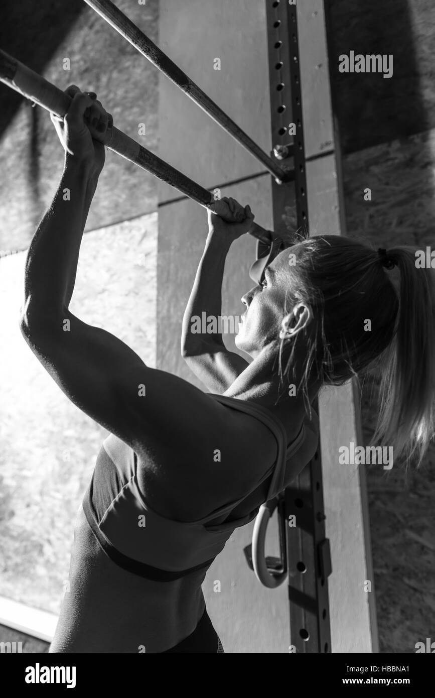 Well built athletic woman doing chin ups - Stock Image