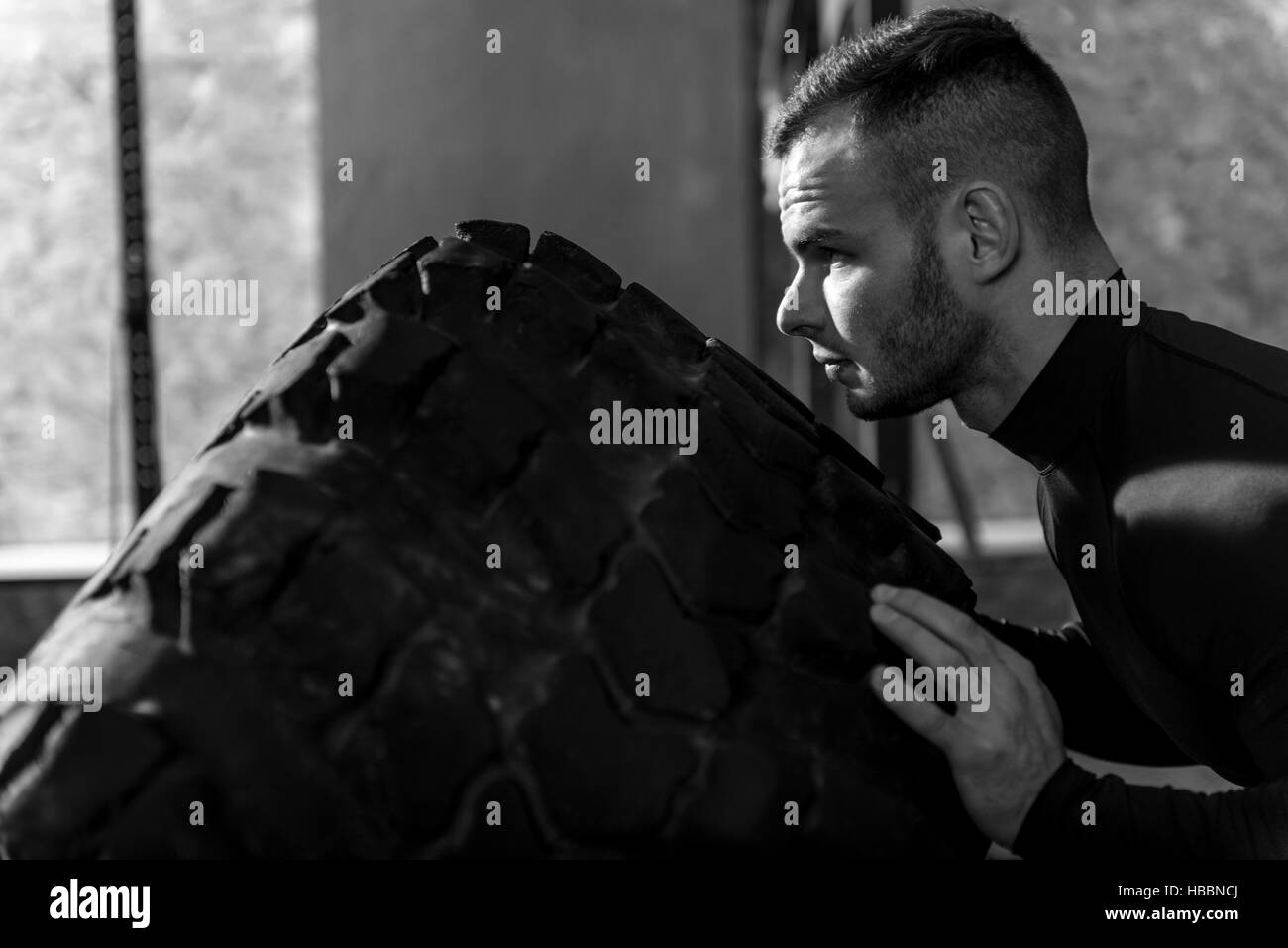 Good looking bearded man pushing the giant tire - Stock Image