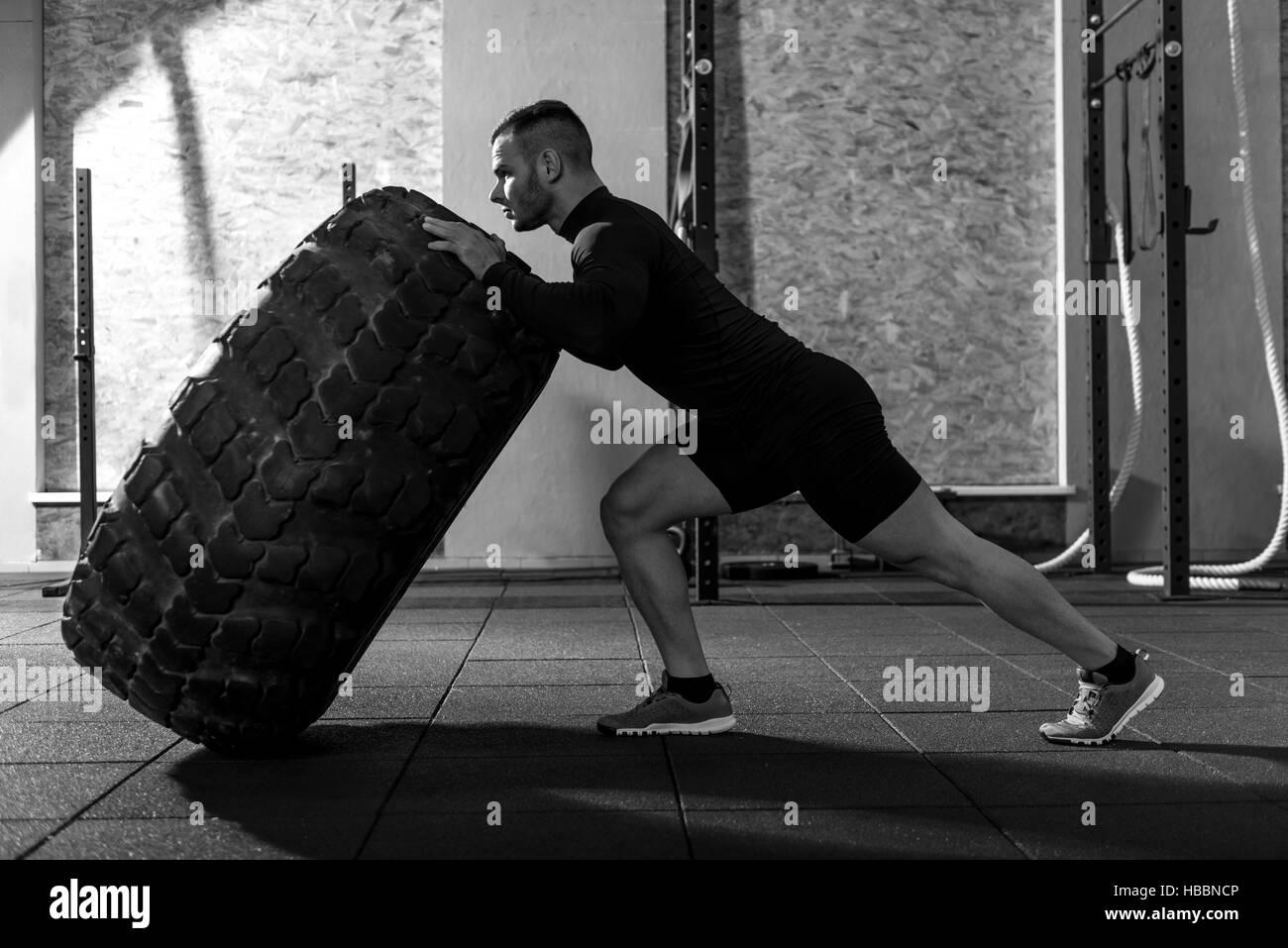 Strong handsome bodybuilder holding a huge tire - Stock Image