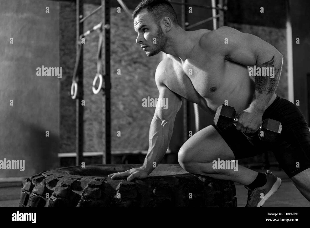 Handsome strong bodybuilder developing his biceps - Stock Image