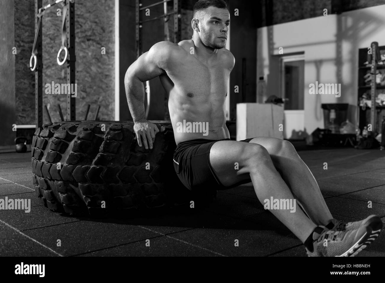 Handsome athletic man building up his muscles - Stock Image
