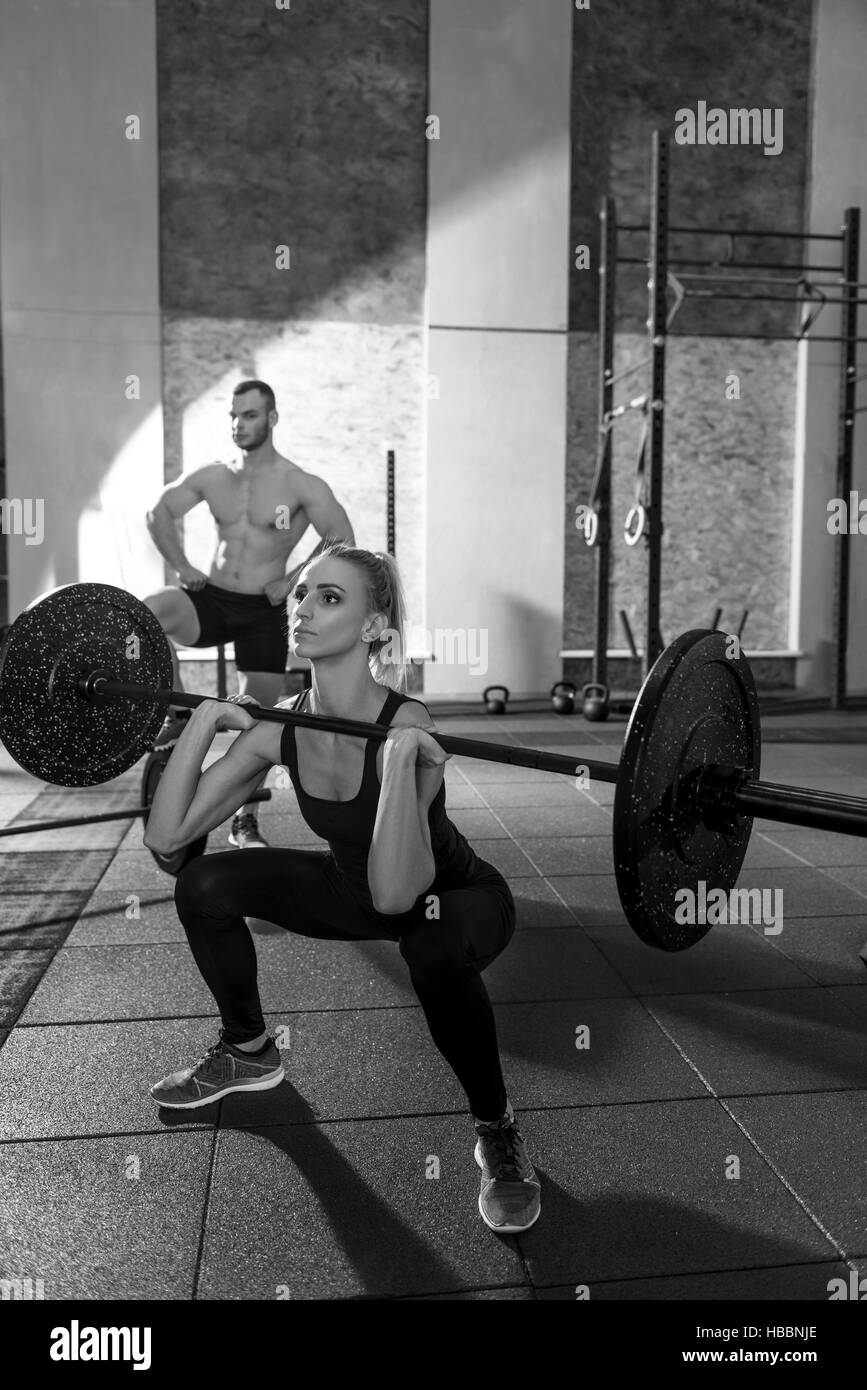 Concentrated athletic woman exercising with a barbell - Stock Image