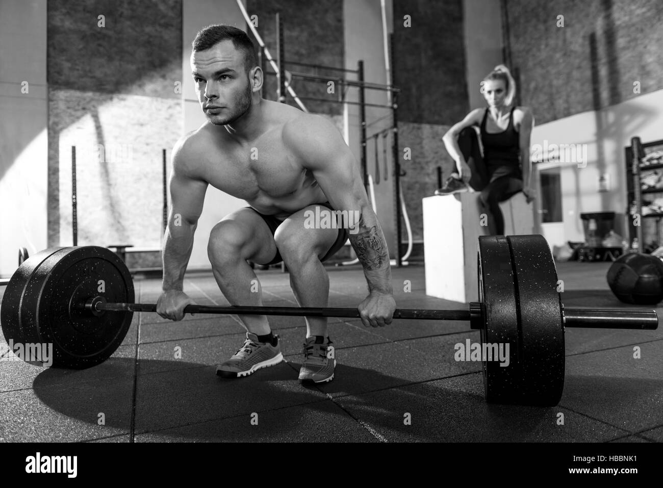 Hard working strong bodybuilder preparing to lift a barbell - Stock Image