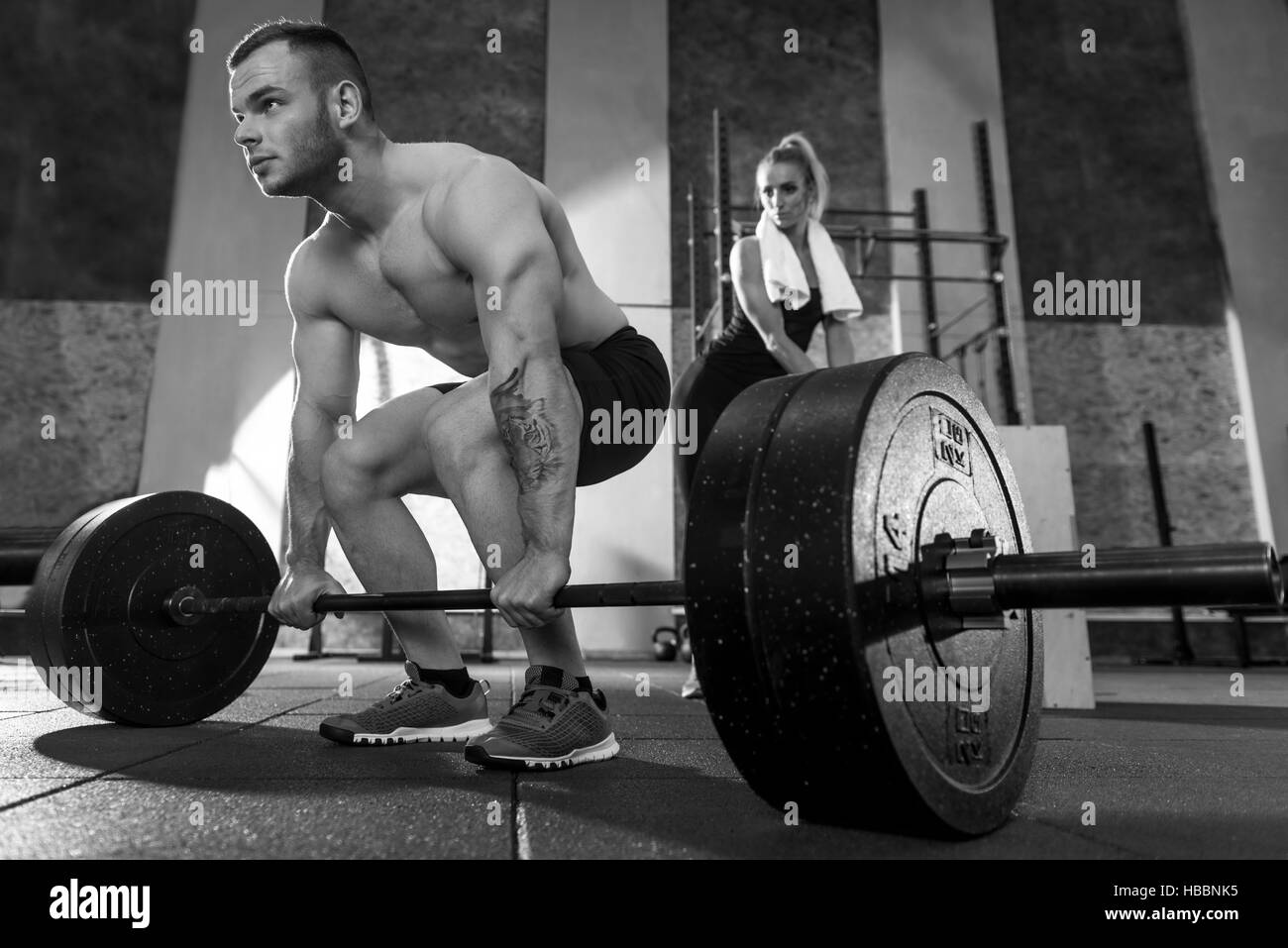 Powerful athletic bodybuilder holding on to the barbell - Stock Image