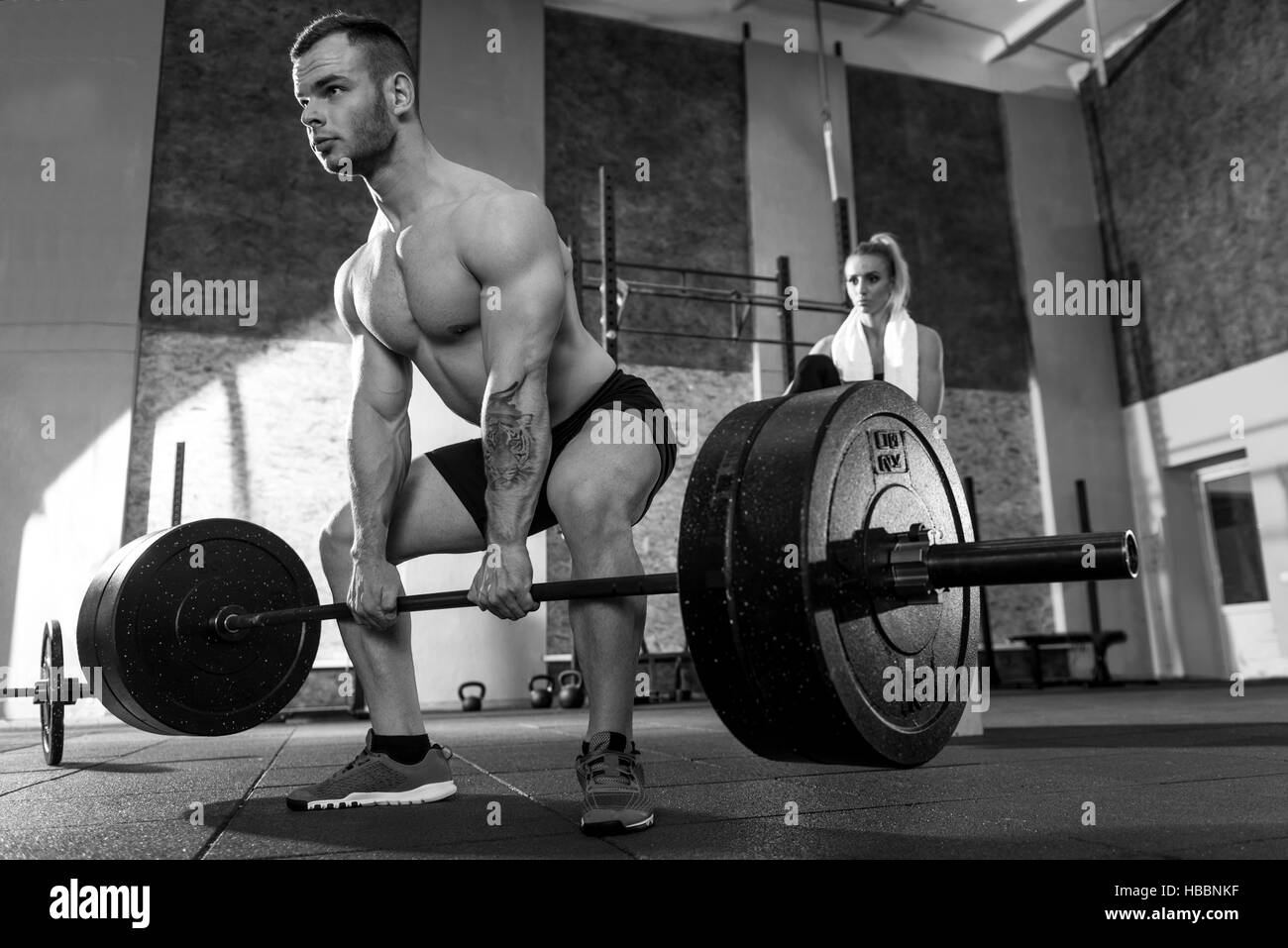 Brutal tattooed man lifting a barbell - Stock Image