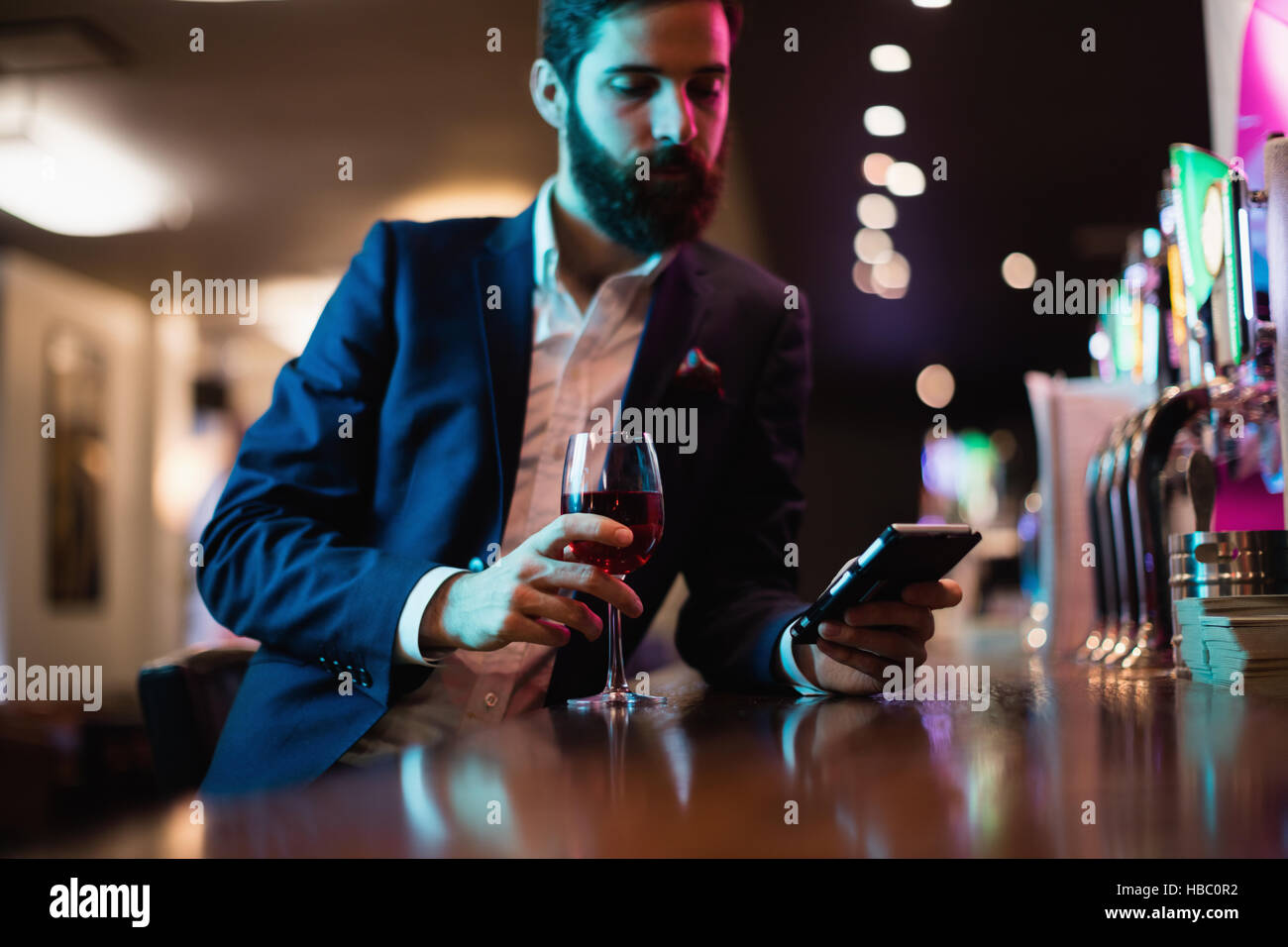 Businessman using mobile phone with glass of red wine in hand Stock Photo