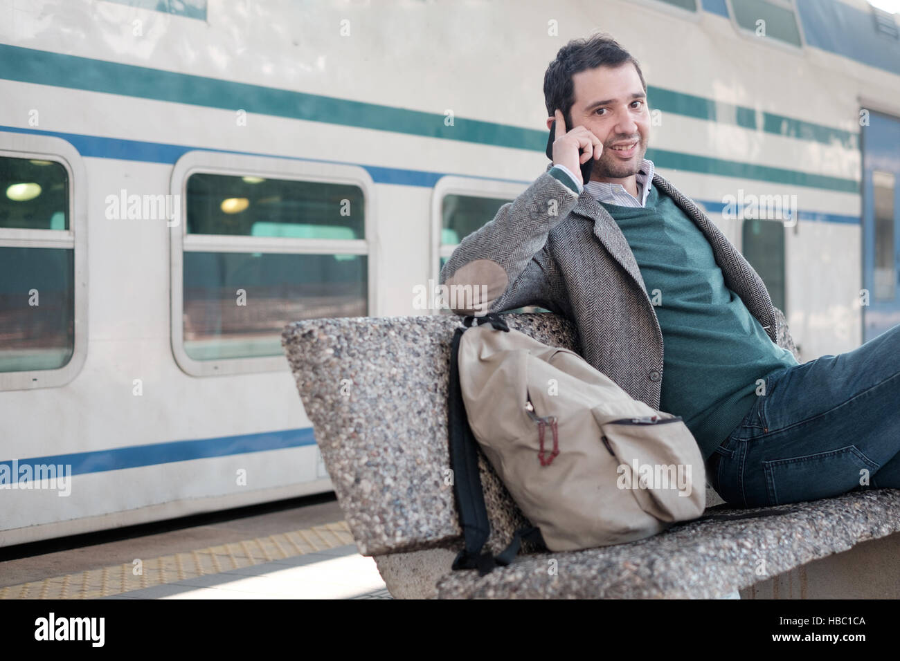 Man talking on the phone in a train station platform - Stock Image