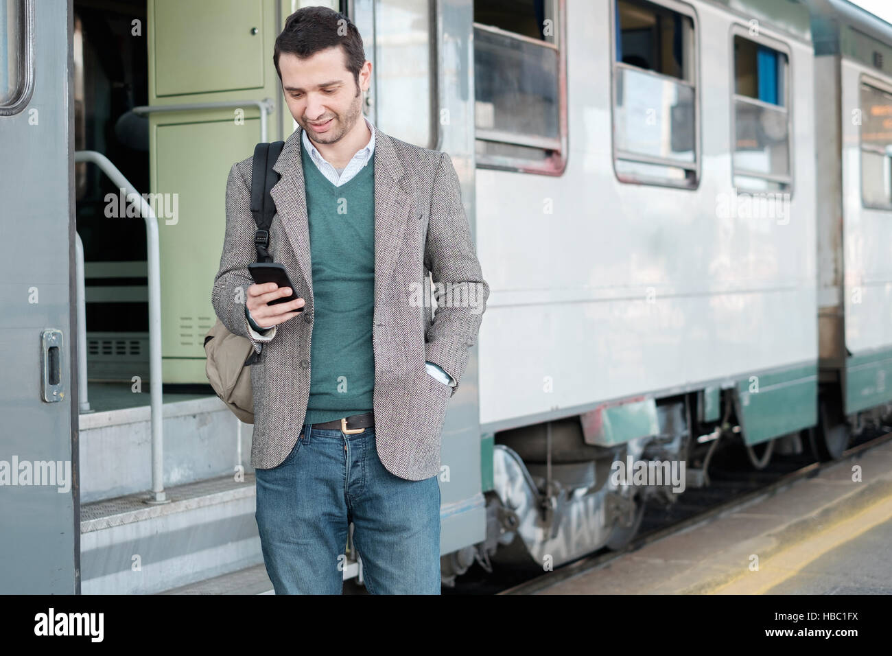 Standing man calling on the phone waiting for the train in a train station platform Stock Photo