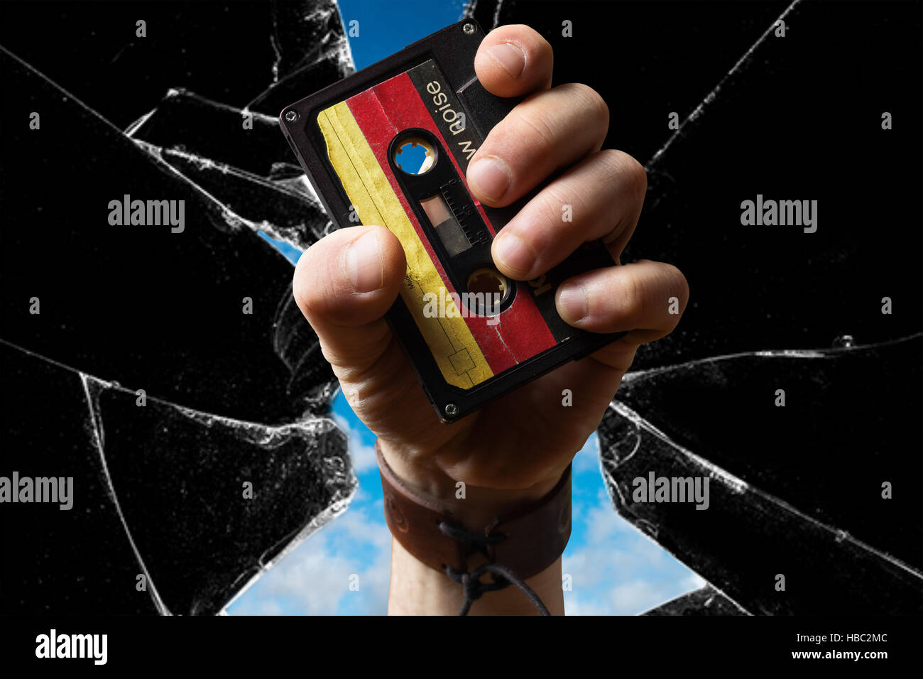 Hand holding east german Musicassette through broken Glass - Stock Image