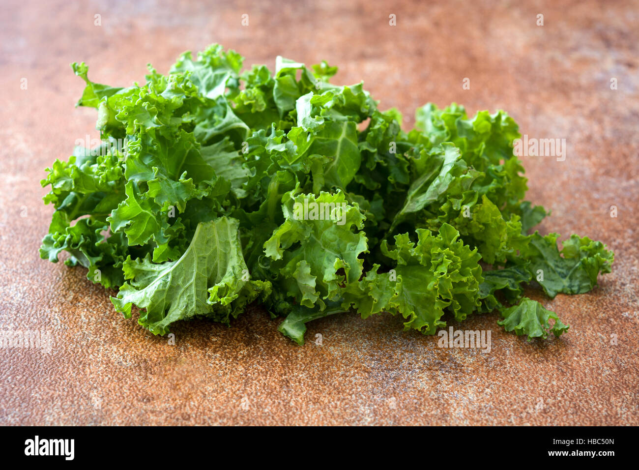 Fresh green superfood kale leaves on rusty background - Stock Image