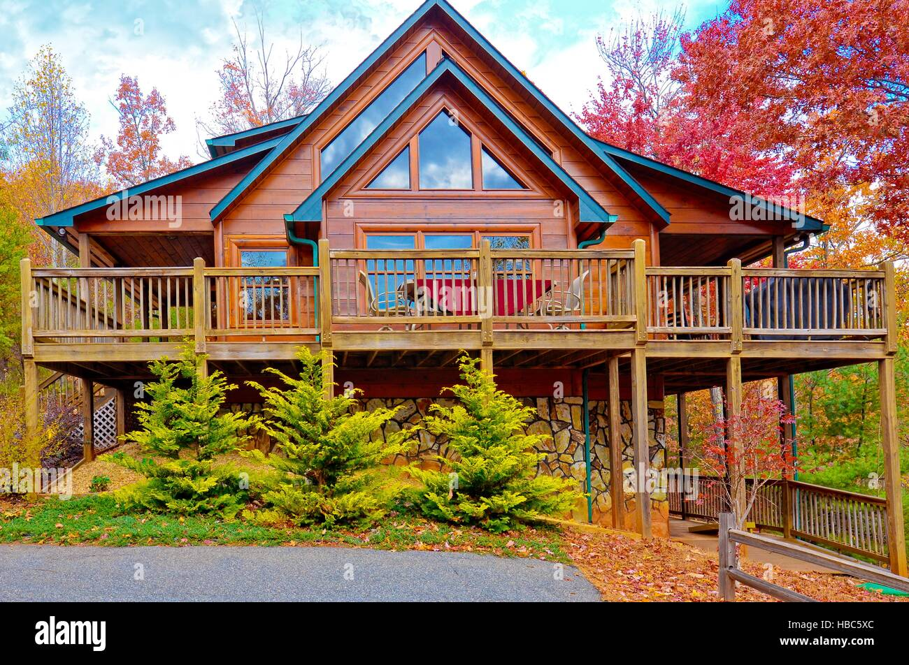 Log house with decks for entertainment surrounded by the colors of autumn. - Stock Image