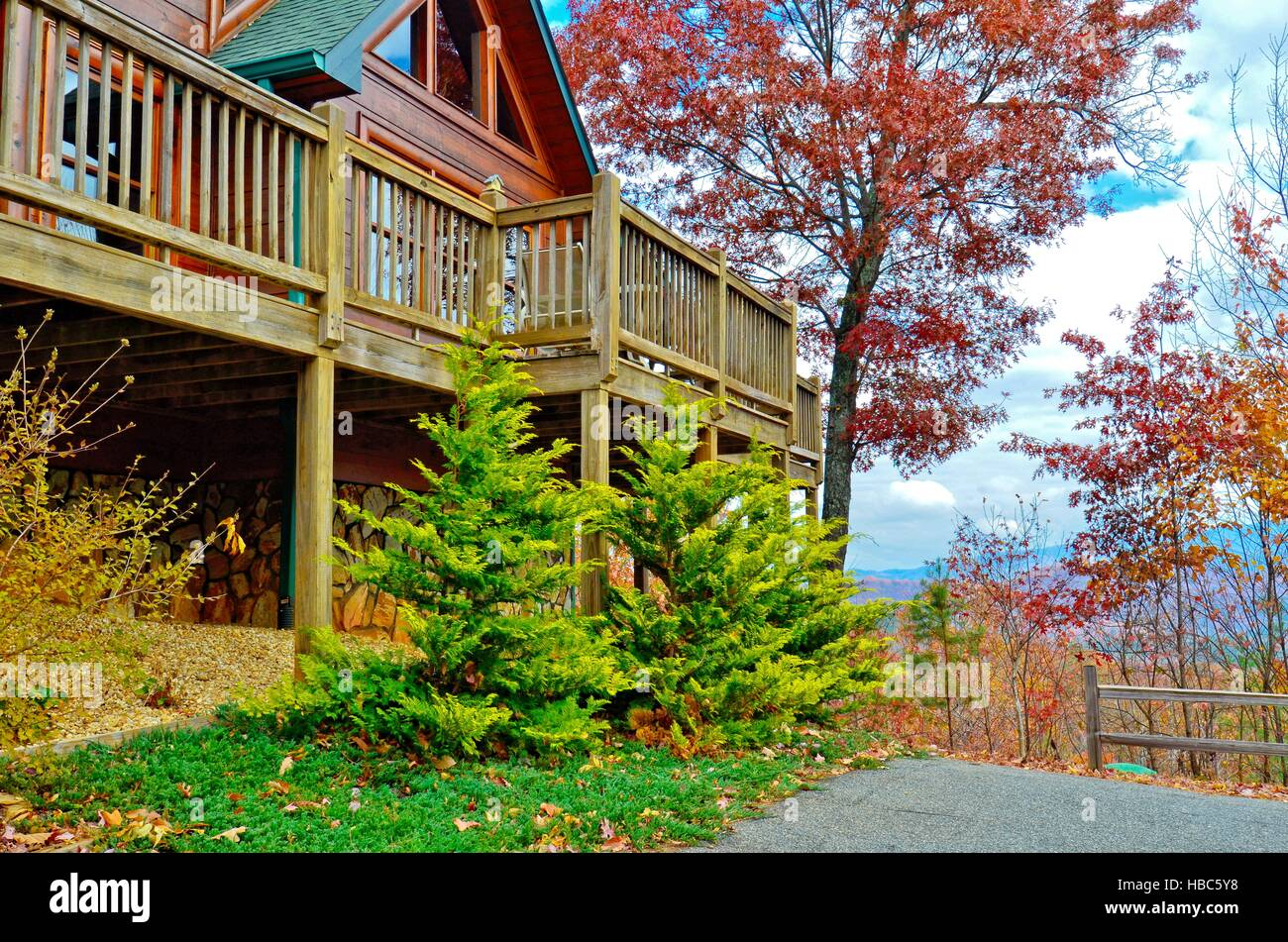 A wooden deck on the side of a log house in the mountains. - Stock Image
