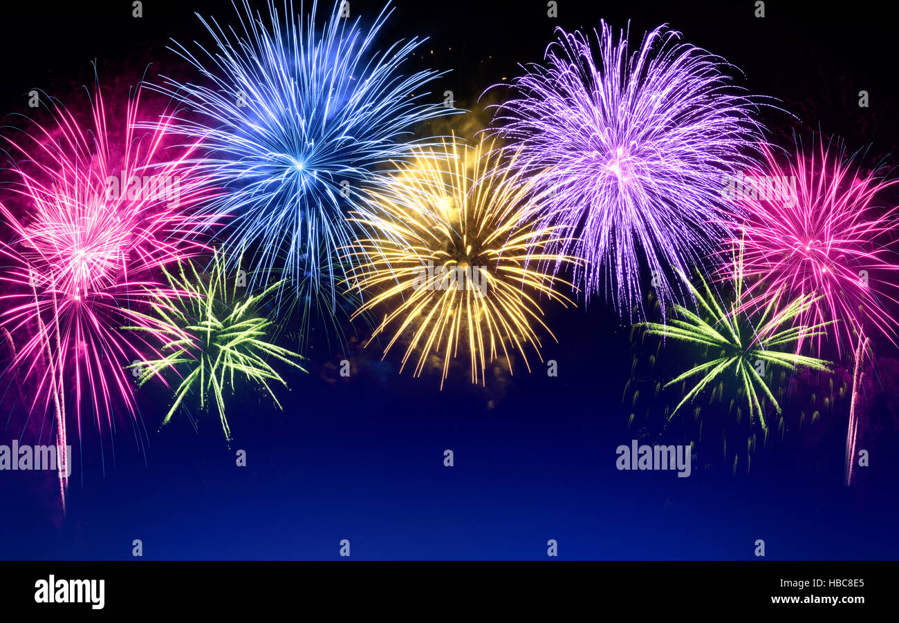 gorgeous multi colored fireworks as an arch shaped border on dark blue background ideal for new year or other celebration events