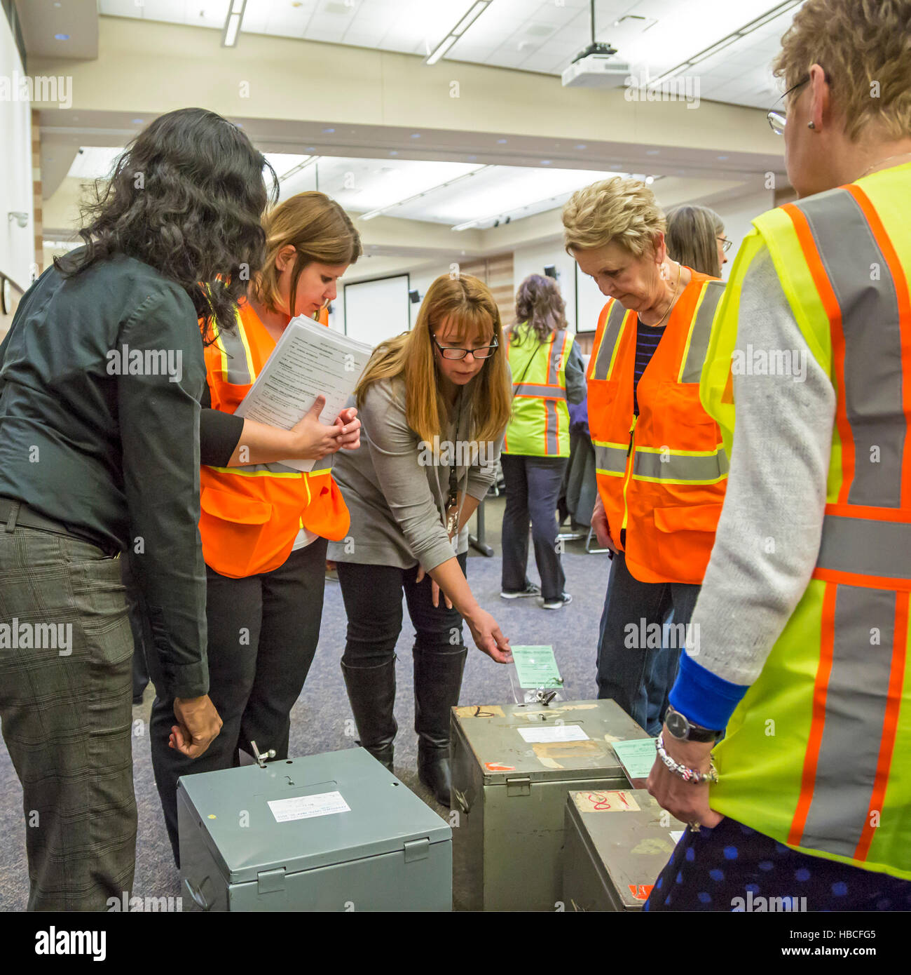 Michigan, USA. 5th December, 2016.Election workers huddle around ballot boxes as votes in the 2016 Presidential - Stock Image