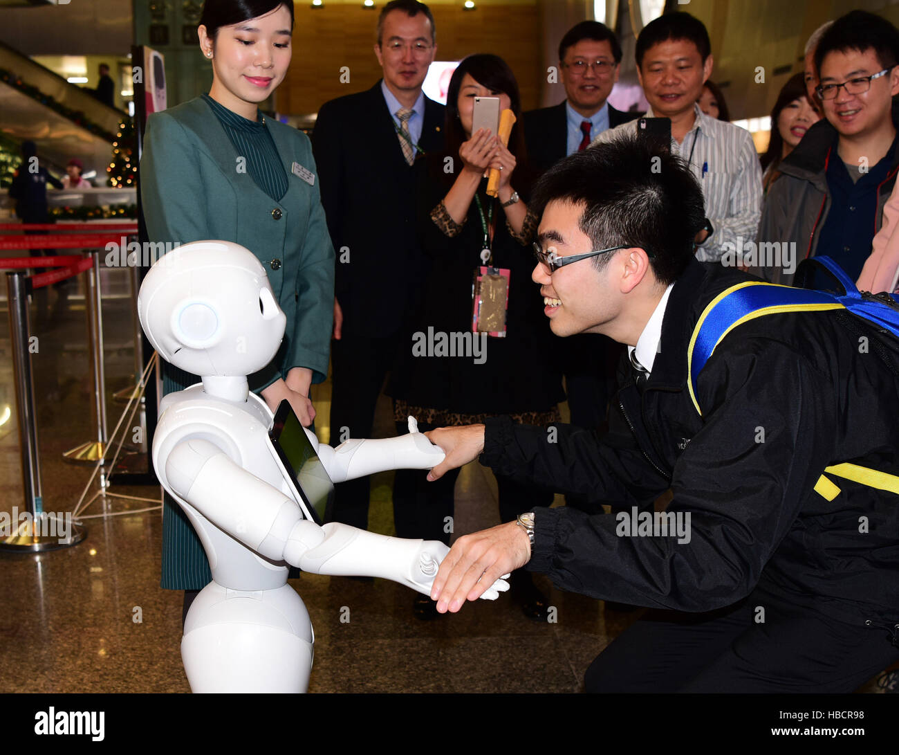 Taipei, Taiwan. 7th Dec, 2016. People interacts with a robot at the Songshan Airport in Taipei, southeast China's - Stock Image