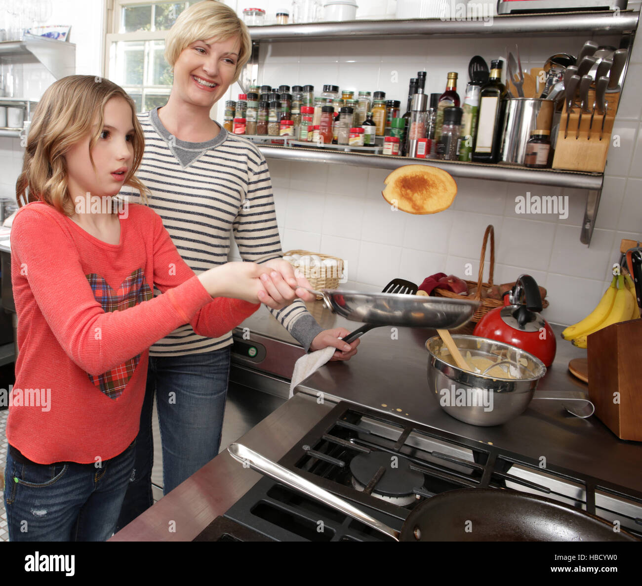 Mother and daughter in kitchen, daughter flipping pancake - Stock Image