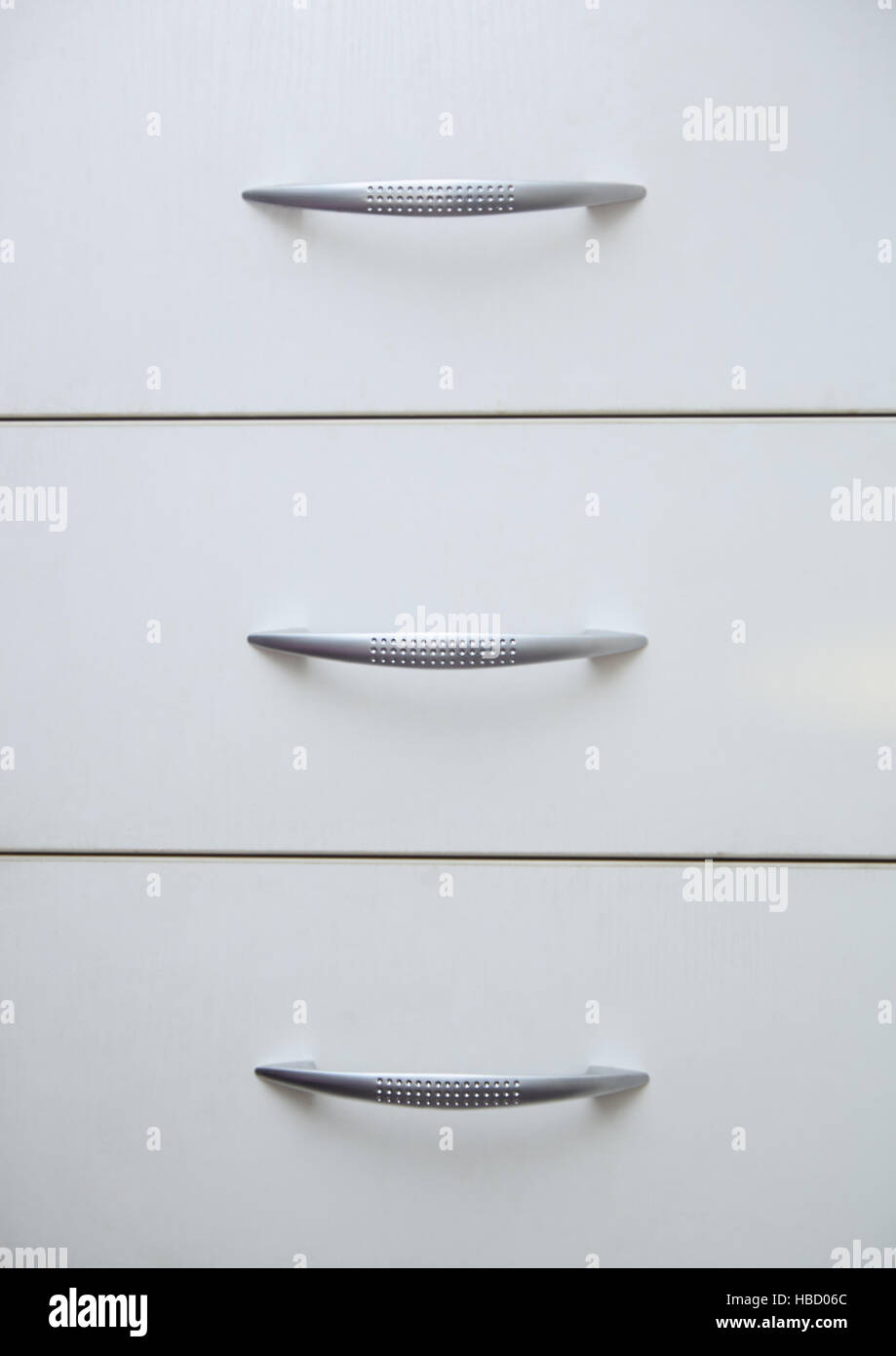 Cabinet with sliding trays and chrome handles - Stock Image