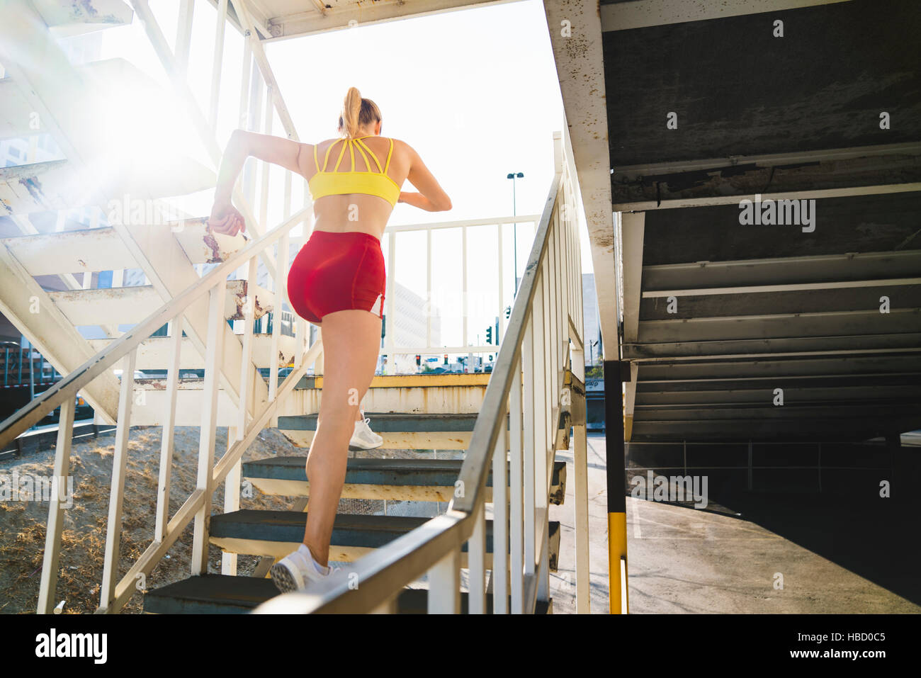 Young woman exercising in urban environment, running up stairs, rear view Stock Photo