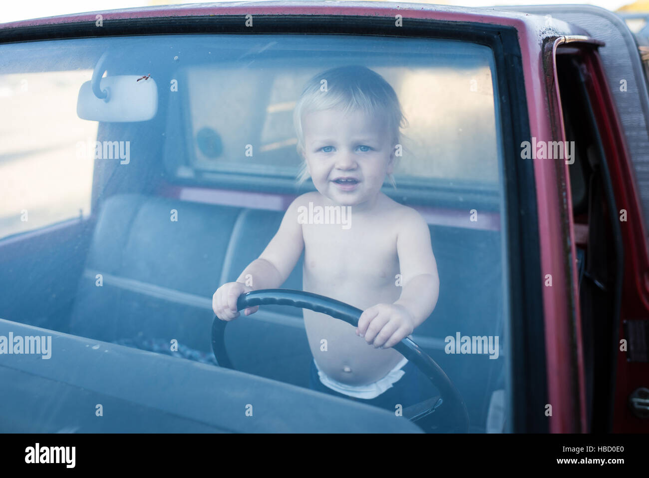 Portrait of male toddler standing in truck holding steering wheel - Stock Image