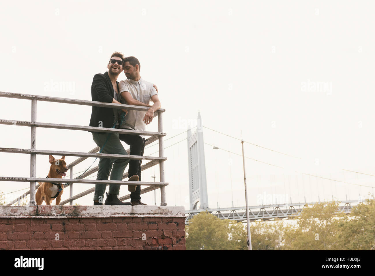 Affectionate young male couple on riverside with dog, Astoria, New York, USA - Stock Image