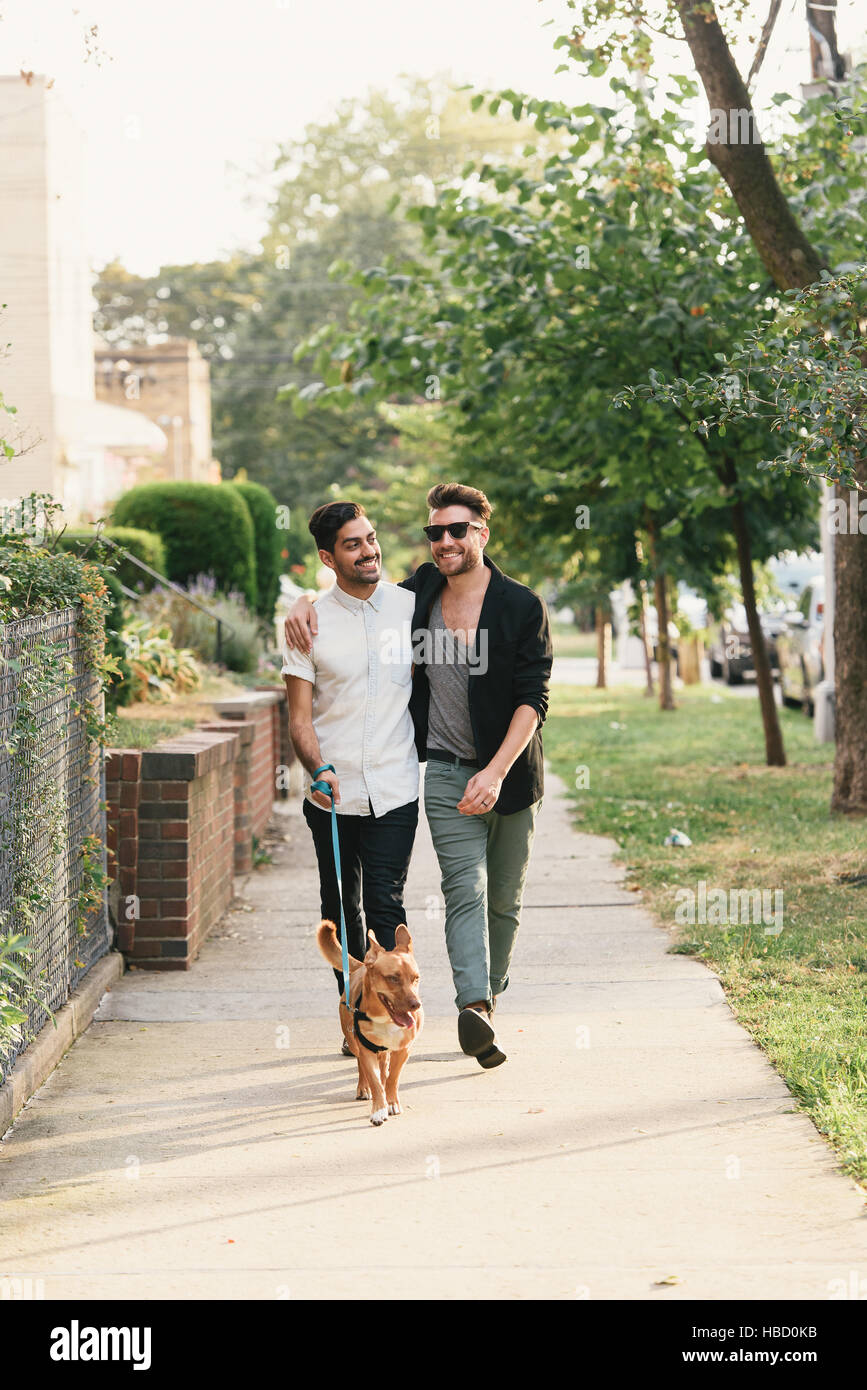 Young male couple walking dog on suburban sidewalk - Stock Image