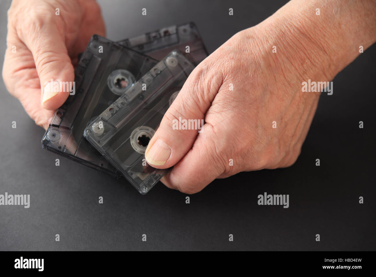 Senior man with three old cassette tapes on a dark background with copy space - Stock Image