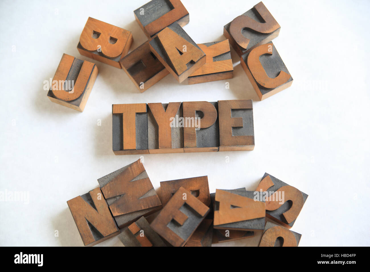 Old letterpress wood letters form the word type on white with other alphabet letters alongside - Stock Image
