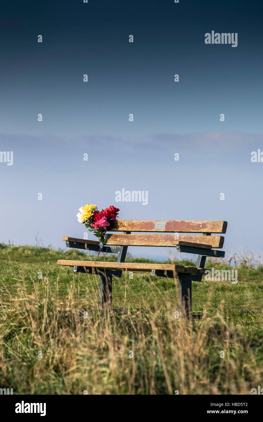 A bouquet of flowers left on a memorial bench in Newquay, Cornwall, England, UK. - Stock Image