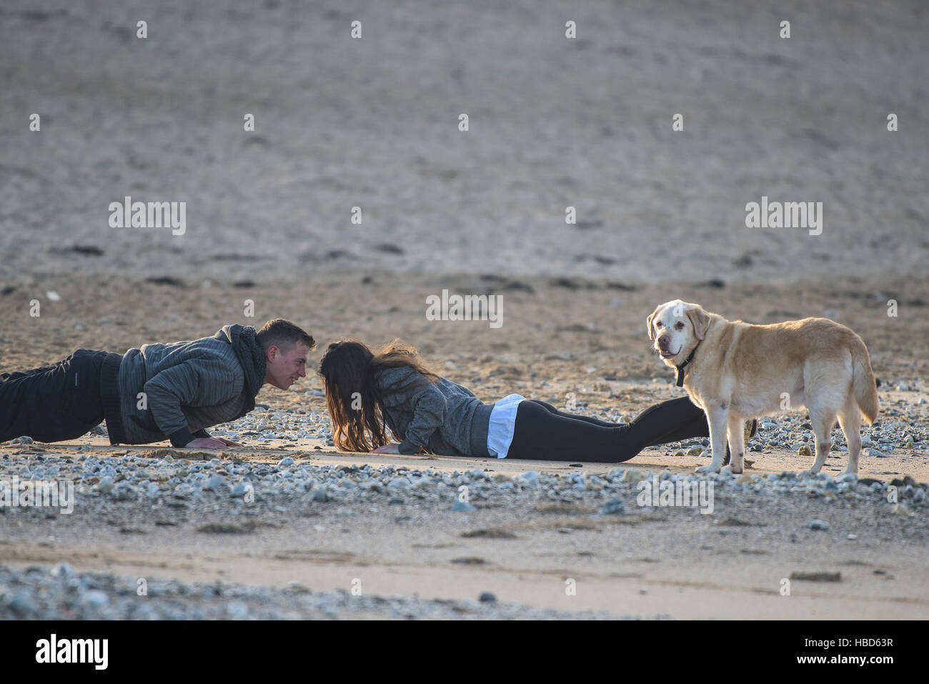 A young couple have fun as they work out on Fistral Beach. - Stock Image