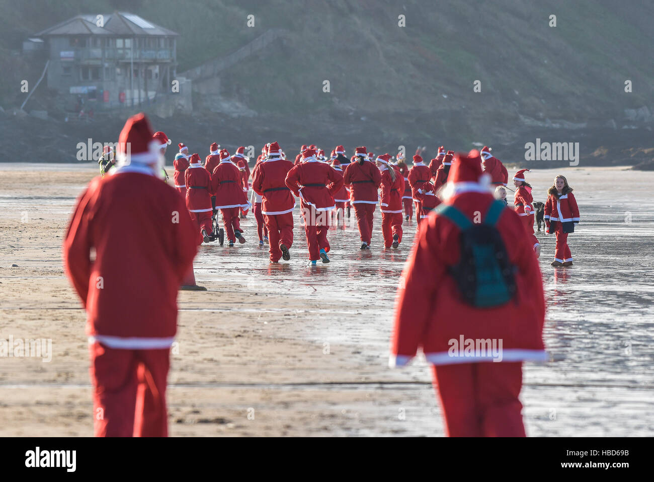 Hundreds of Santas turn out for a fund-raising fun run across a chilly Fistral Beach in the annual Santa Run on - Stock Image