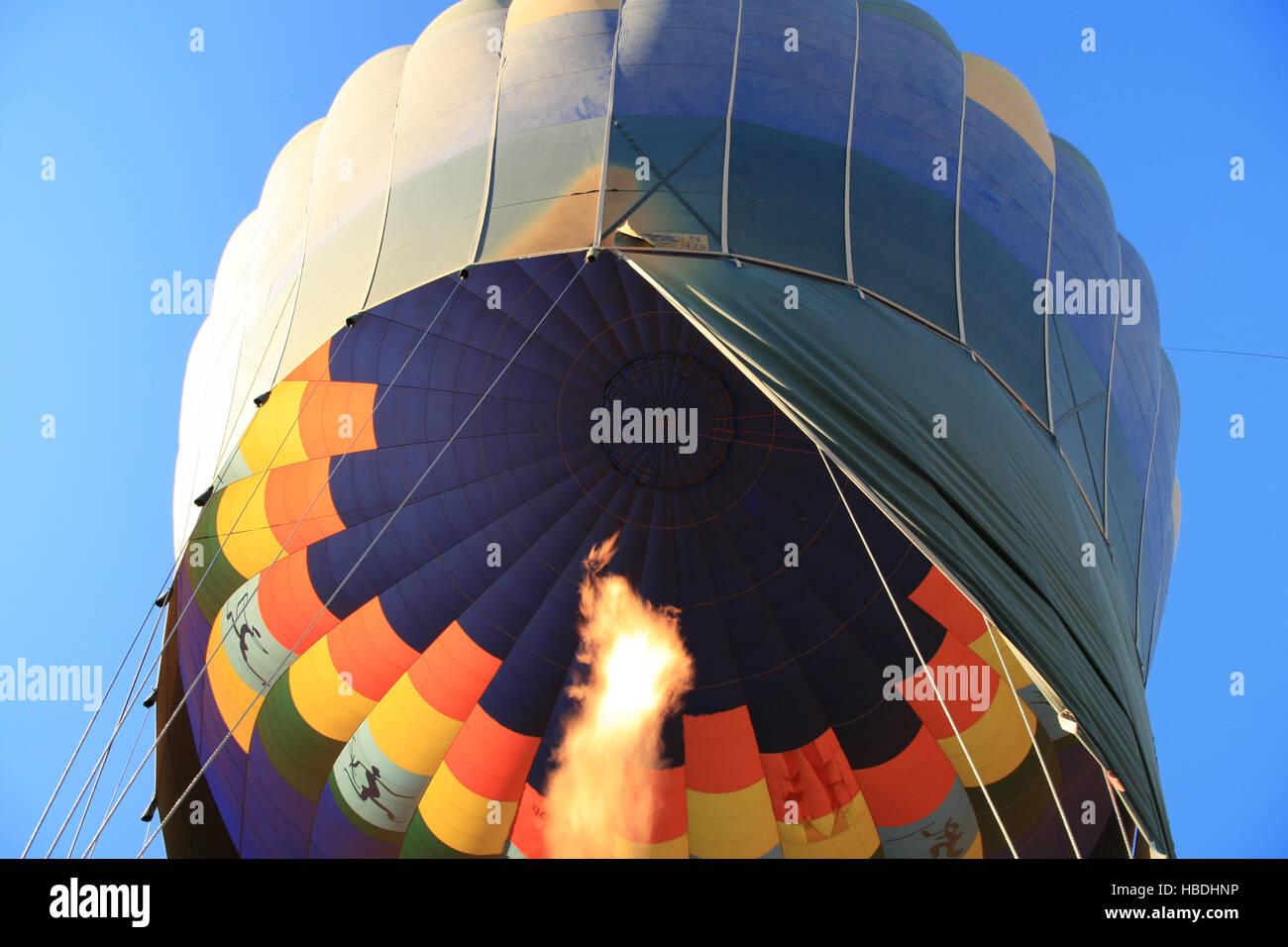 Flame warming a hot air balloon as it rises into a clear blue sky Stock Photo