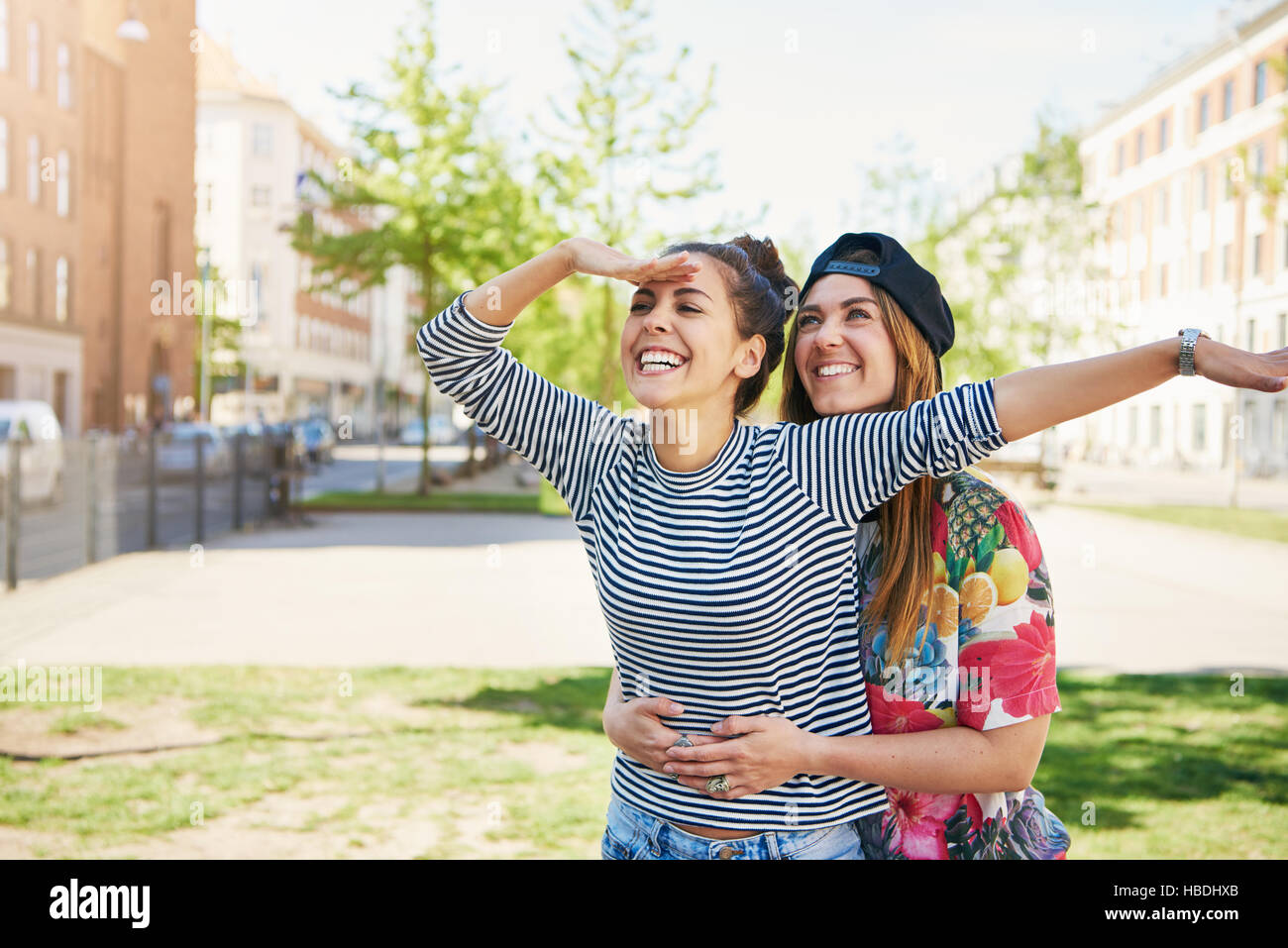 Pair of joyful loving sisters embracing and looking to outward and to the side with gesture as if to find something Stock Photo