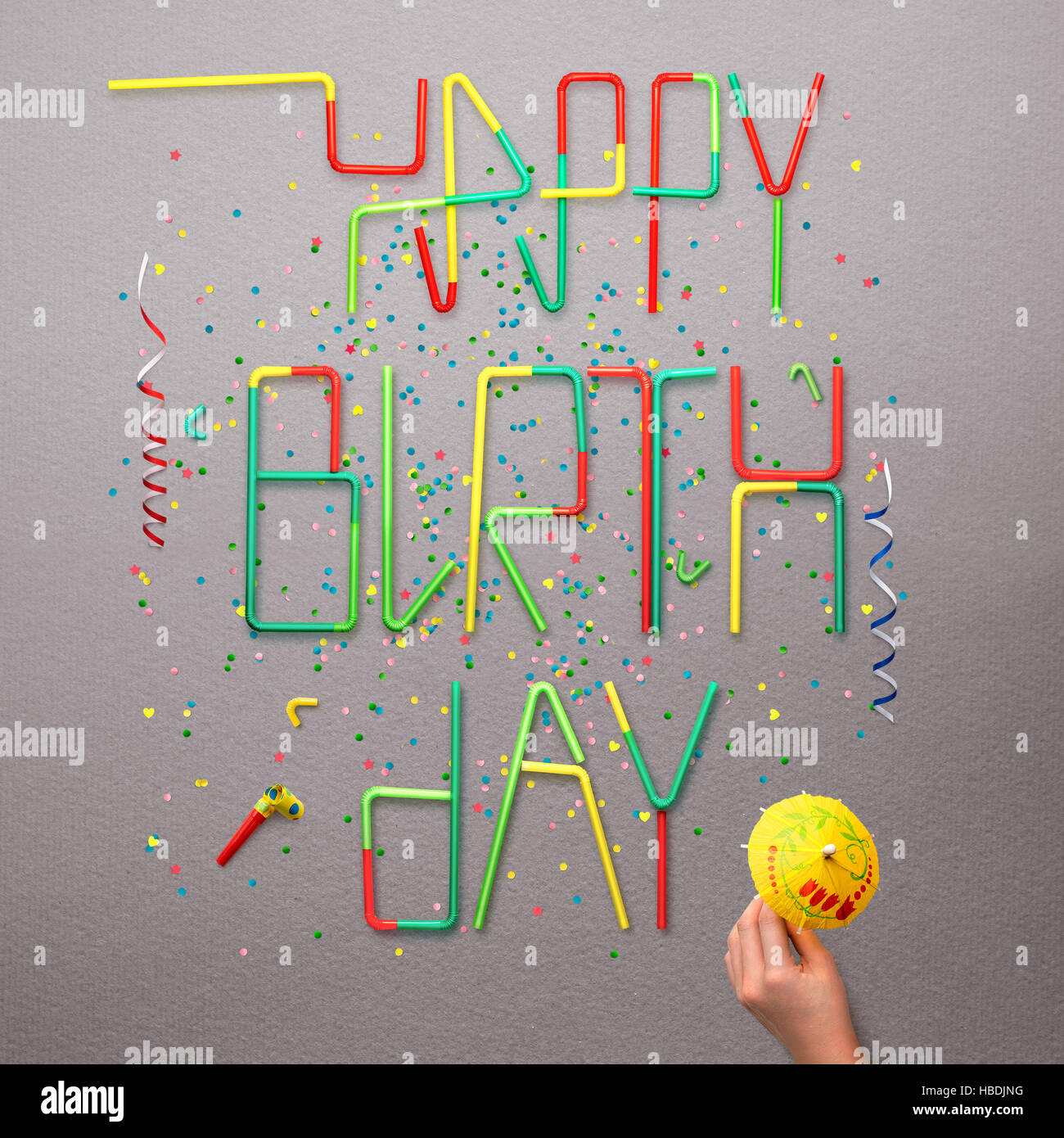 Creative still life photo of happy birthday sign made of cocktail straws with confetti and serpentine on grey background. - Stock Image