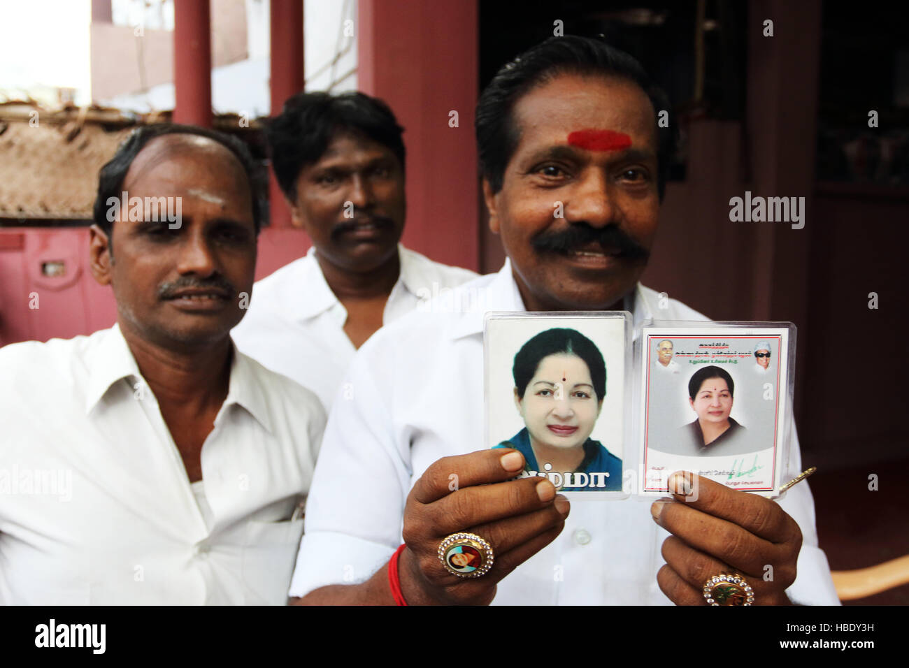 Devotees of Jayalalitha Jayaraman, former actress, state minister of Tamil Nadu, pose with photos of their political - Stock Image